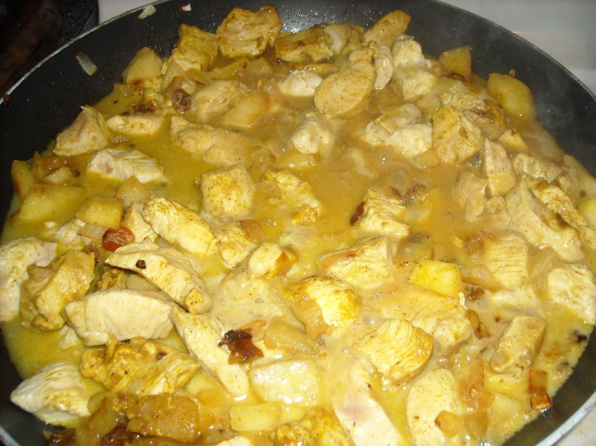 Curried chicken with  apples, raisins, onion, and spices simmering in coconut milk and chicken broth