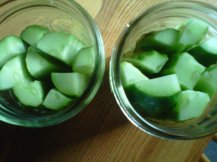 Cut cucumbers and place into the jars. They should fit tightly but not be squashed.